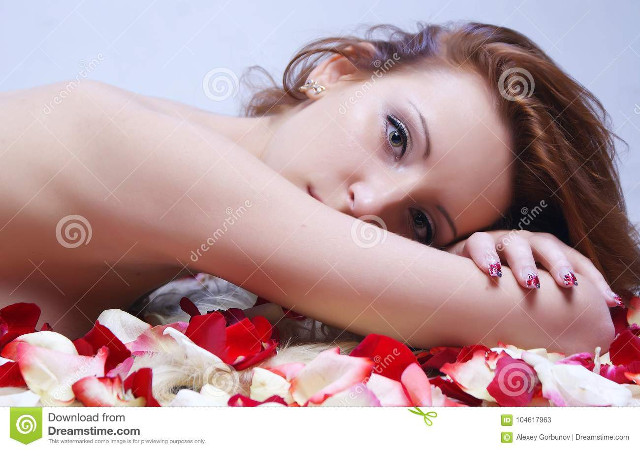 Beautiful young girl posing against the background of rose petal
