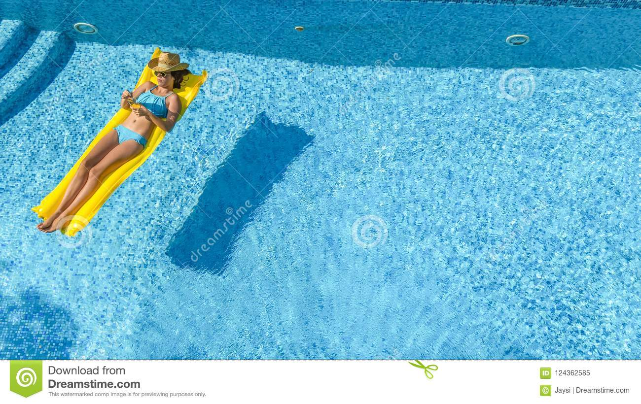 Beautiful young girl relaxing in swimming pool, swims on inflatable mattress and has fun in water on family vacation, aerial view