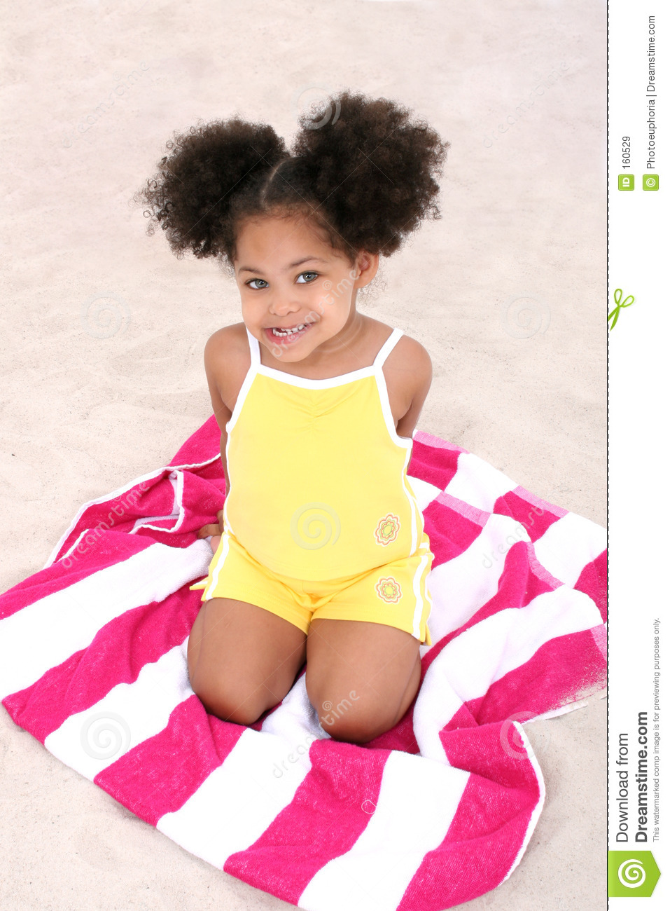 Beautiful Young Girl Sitting On Beach Towel In The Sand