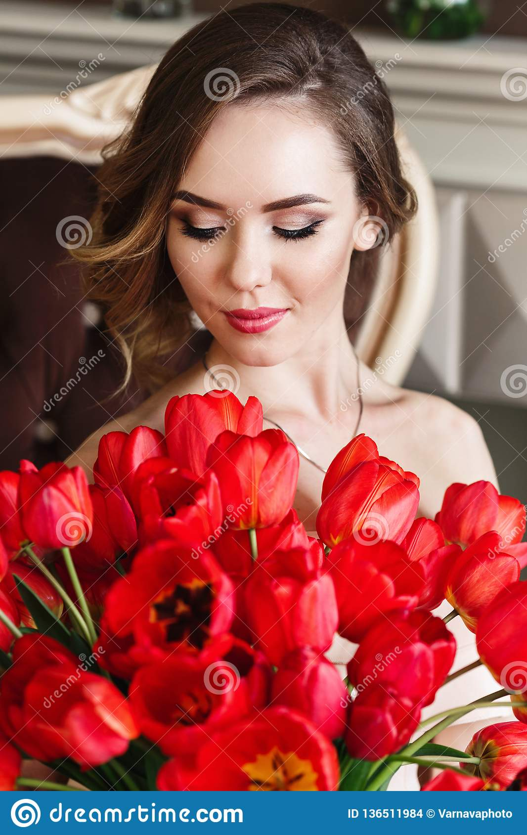 A beautiful young girl is sitting on the sofa and holding a large bouquet of red tulips. March 8 concept. Morning of the bride.