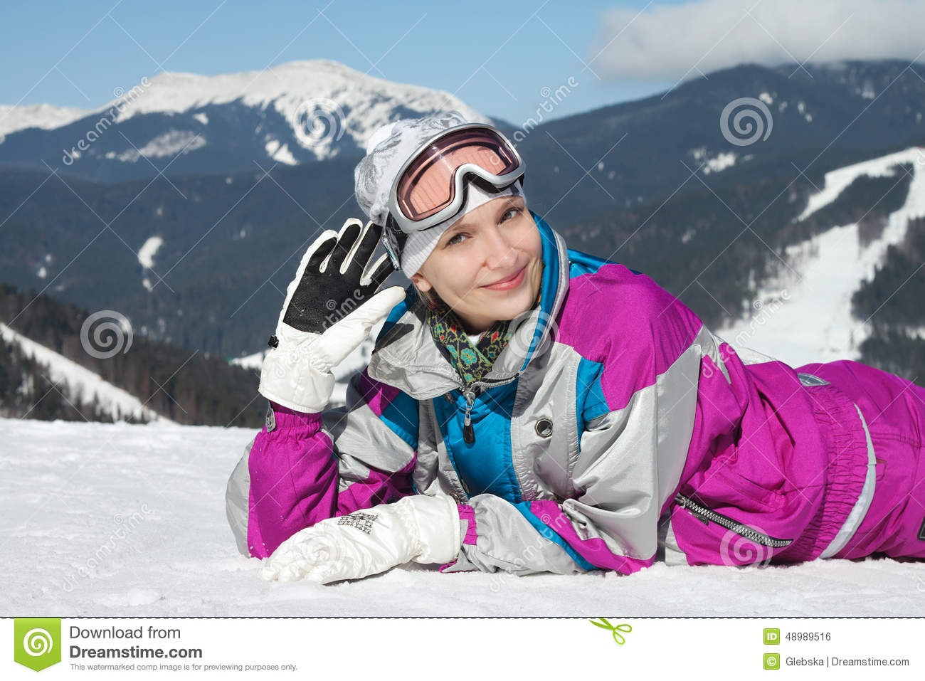 Beautiful Young Girl In Ski Suit Lying In The Snow Stock Photo ... b70ba21c5