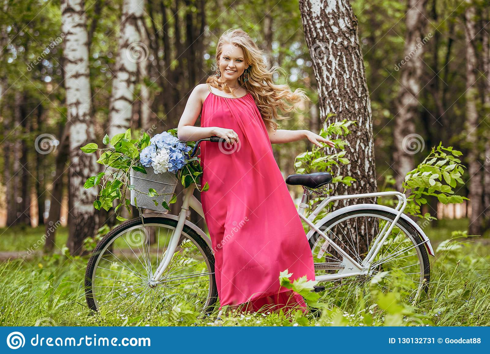 Beautiful young girl in a summer dress at sunset. Fashion photo in the forest. Model on a bicycle with flower bouquet, in a pink l