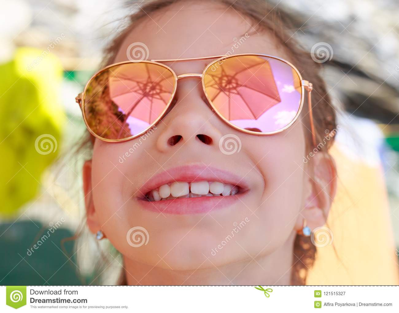 Beautiful young girl in sunglasses with beach umbrella reflection.