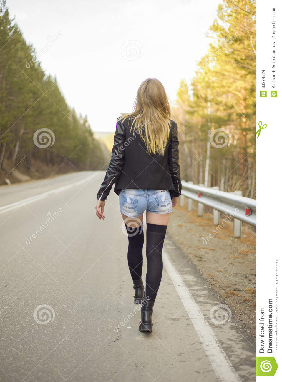 Beautiful Girl Walking Down A Forest Road Stock Photo