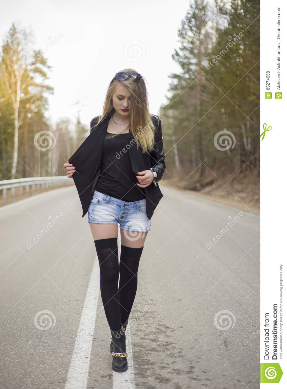 A Woman Takes A Woodland Walk Down Forest Path High-Res