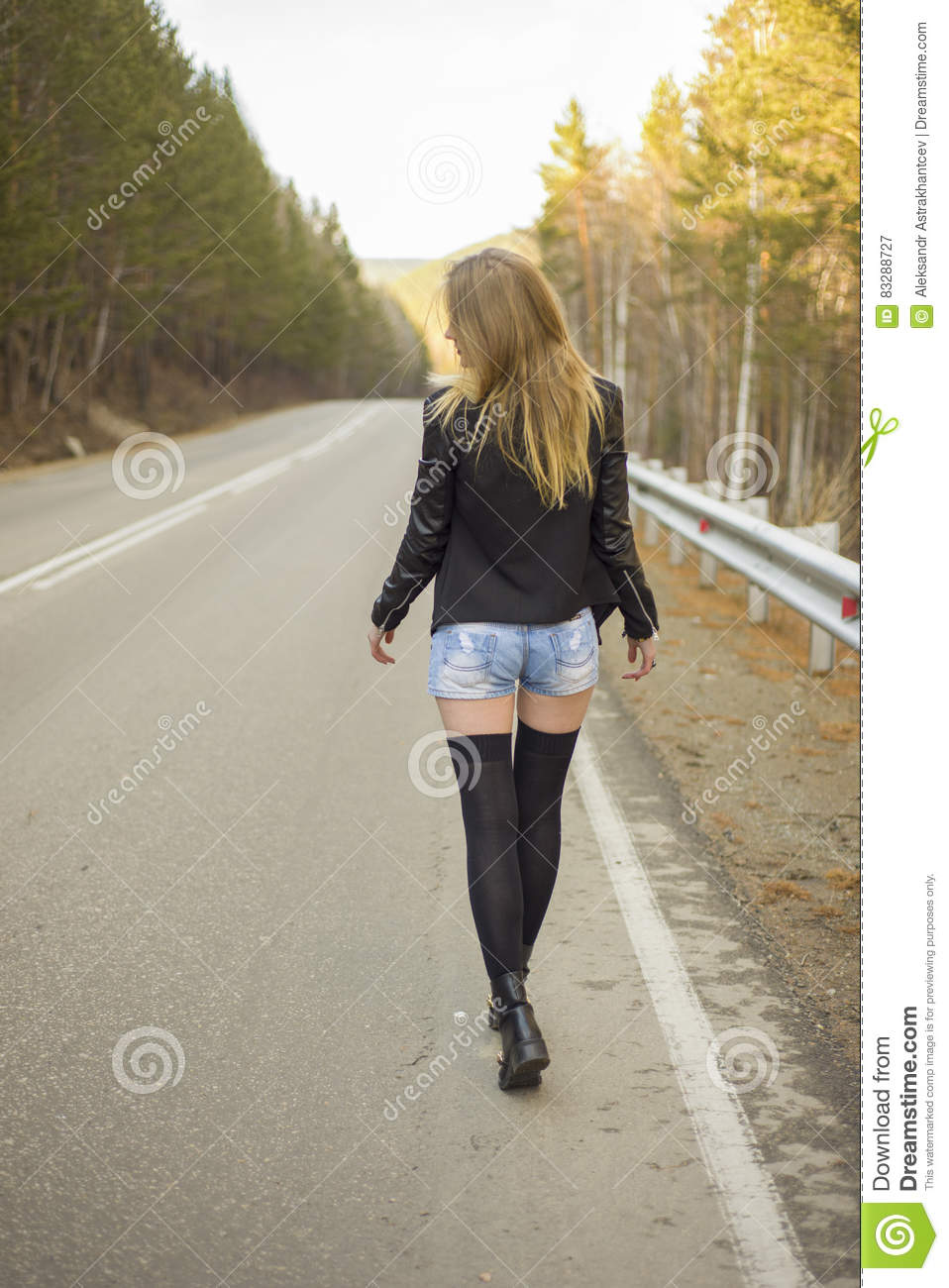 Beautiful Young Girl Walking Down The Road In The Forest