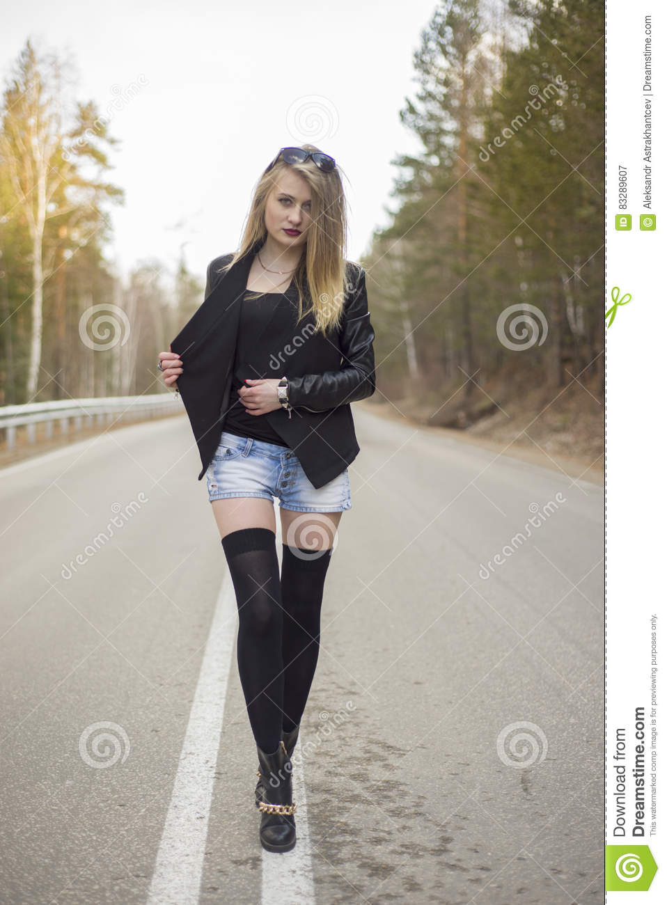Woman Walking In The Rain On Asphalt Forest Road At Autumn