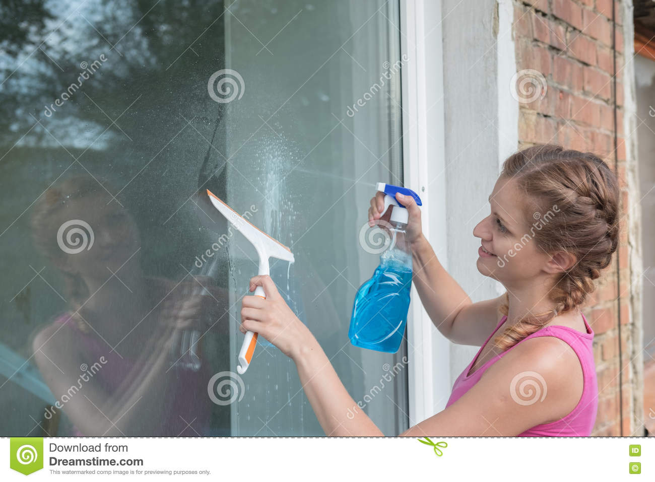 Beautiful young girl washes a window in a brick house