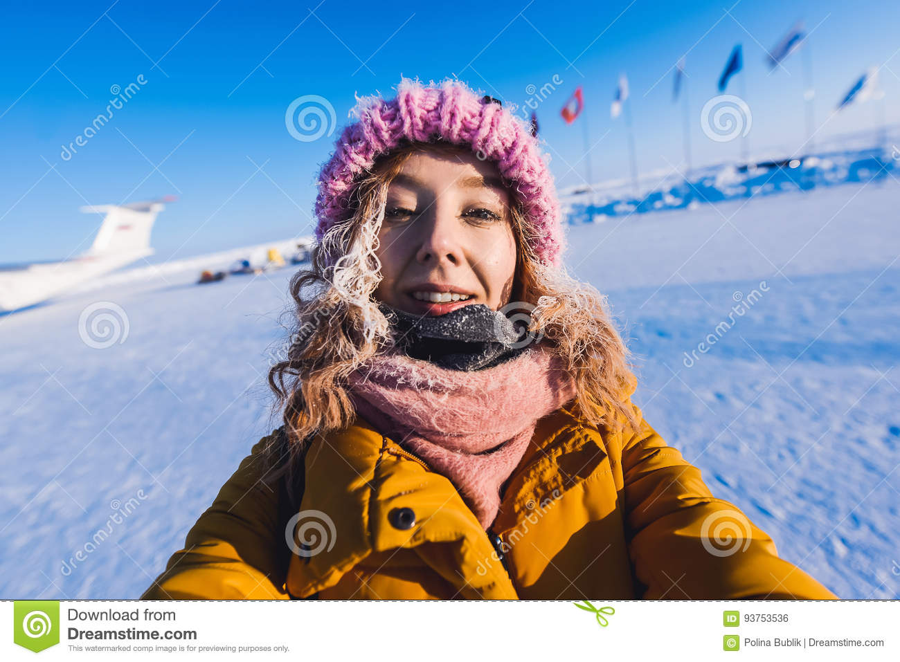 9ef374cee Beautiful Young Girl In A Yellow Down Jacket And Pink Knitted Cap ...