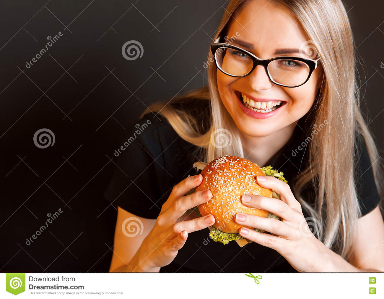 Beautiful young, healthy girl holds a tasty big burge