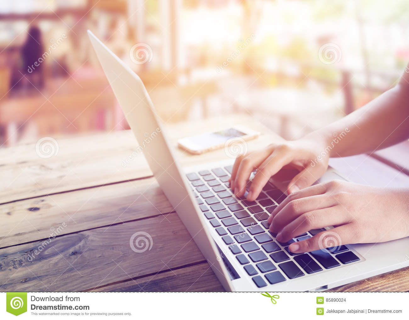beautiful young hipster woman`s hands busy working on her laptop sitting at wooden table in a coffee shop