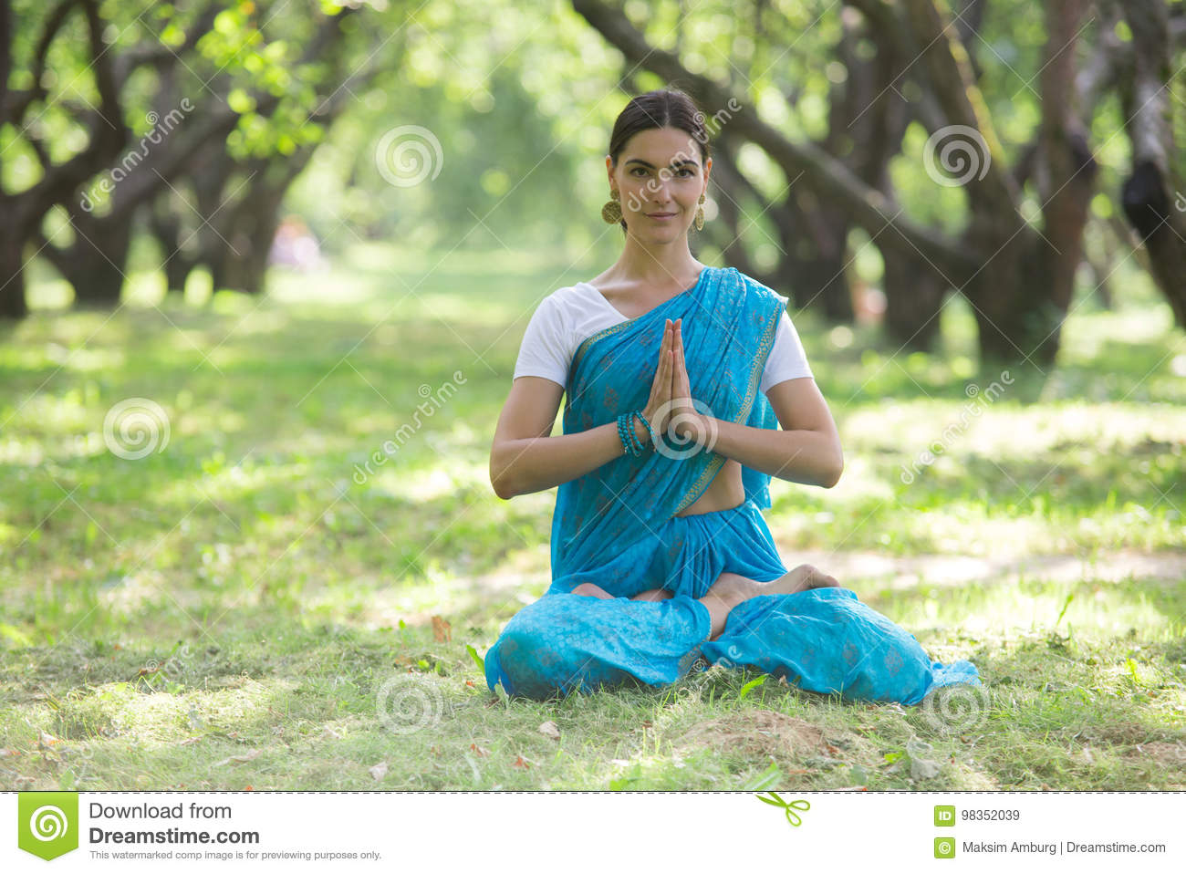 26639c49da Beautiful young woman dressed in a sari praying and meditating in the park  hinduism religion yoga