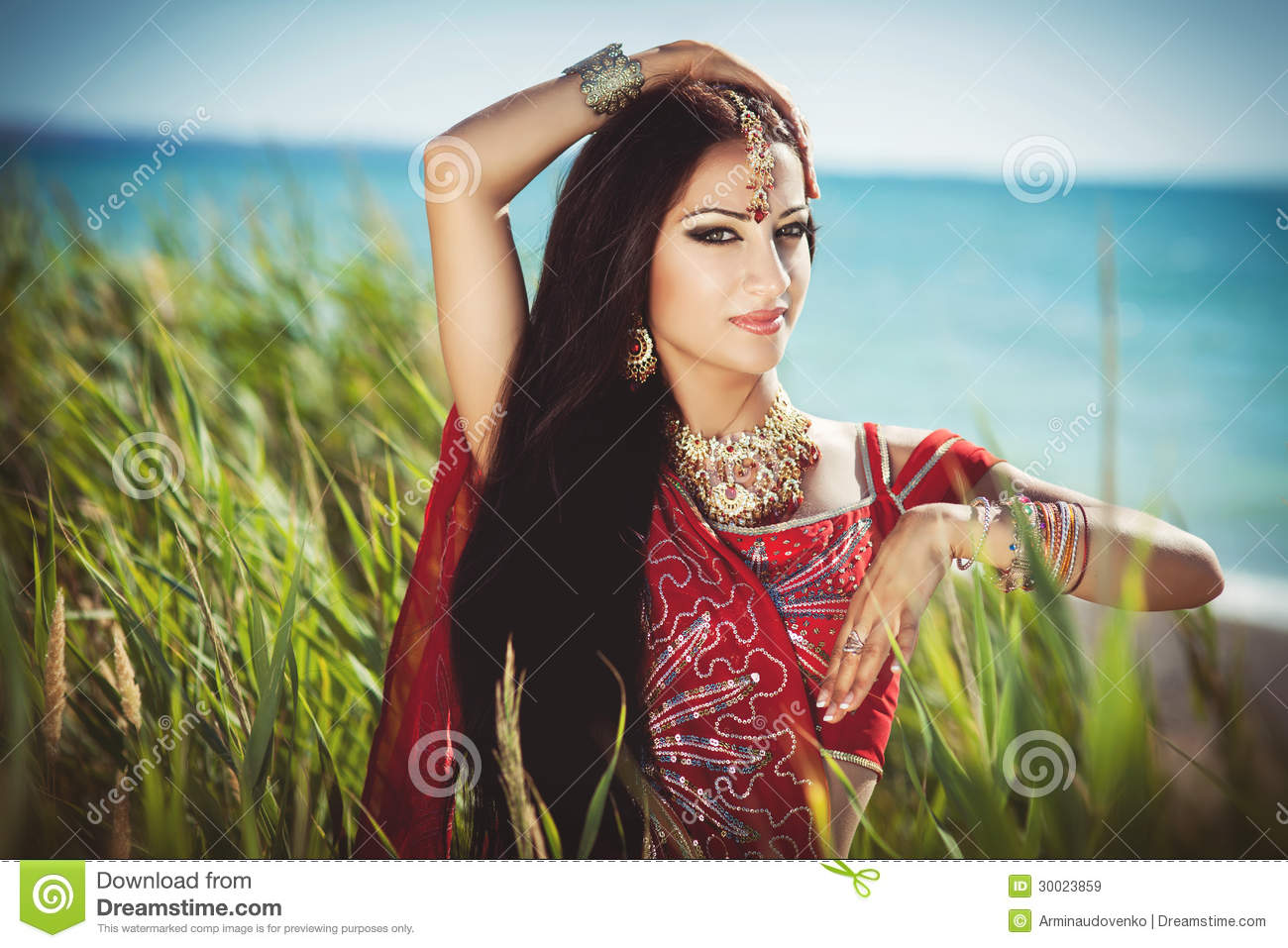 Beautiful young indian woman in traditional clothing with bridal makeup and jewelry. gorgeous brunette bride traditionally dressed Outdoors in India.