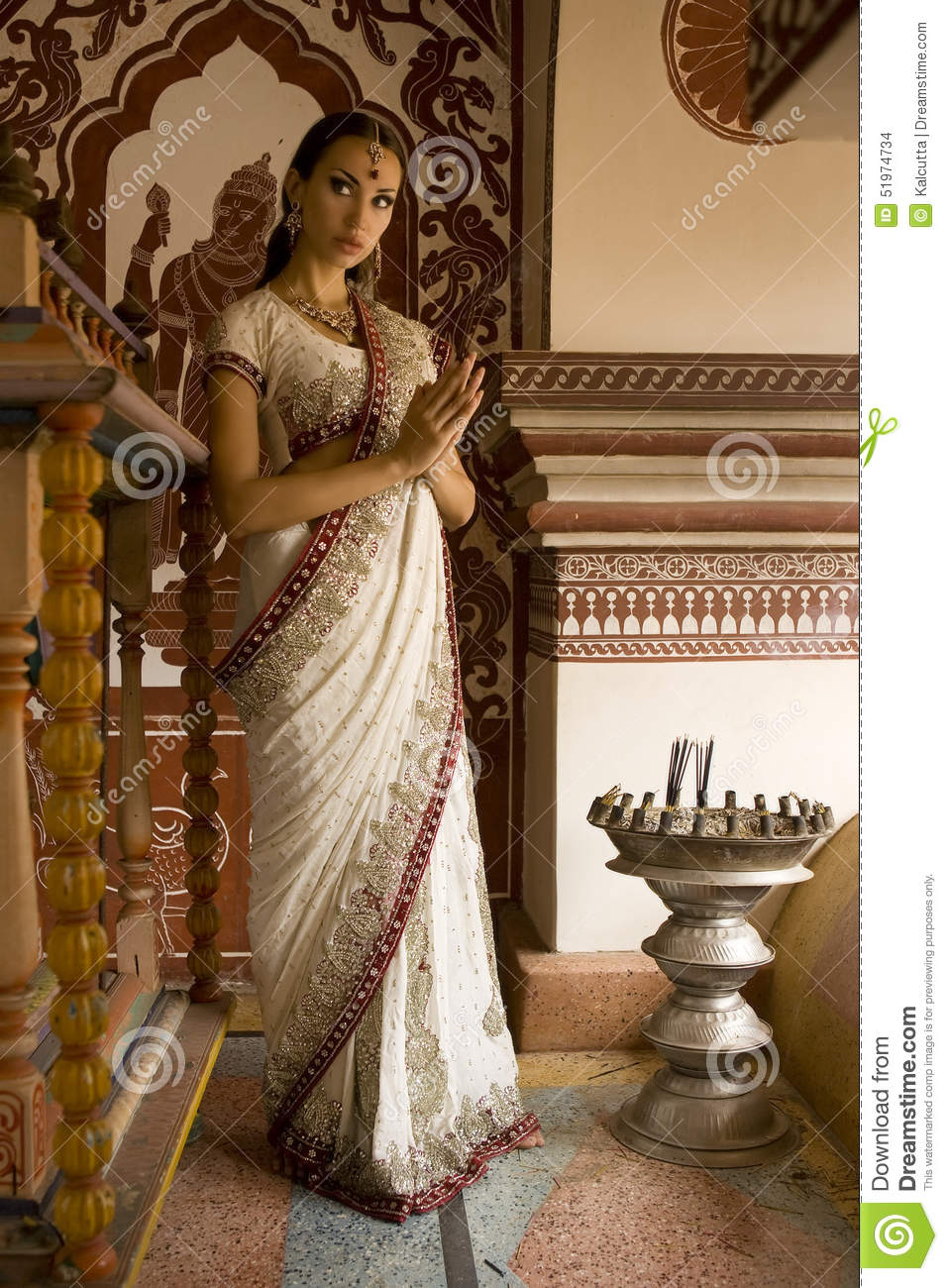 Beautiful young indian woman in traditional clothing with incens
