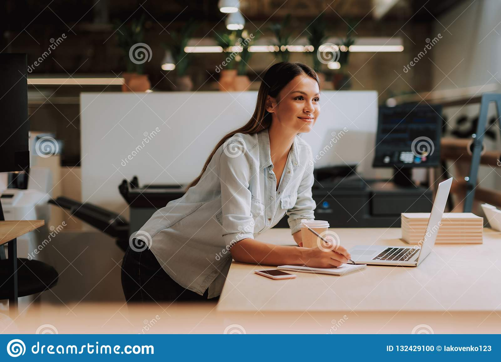 Beautiful young lady with hot drink working at modern office
