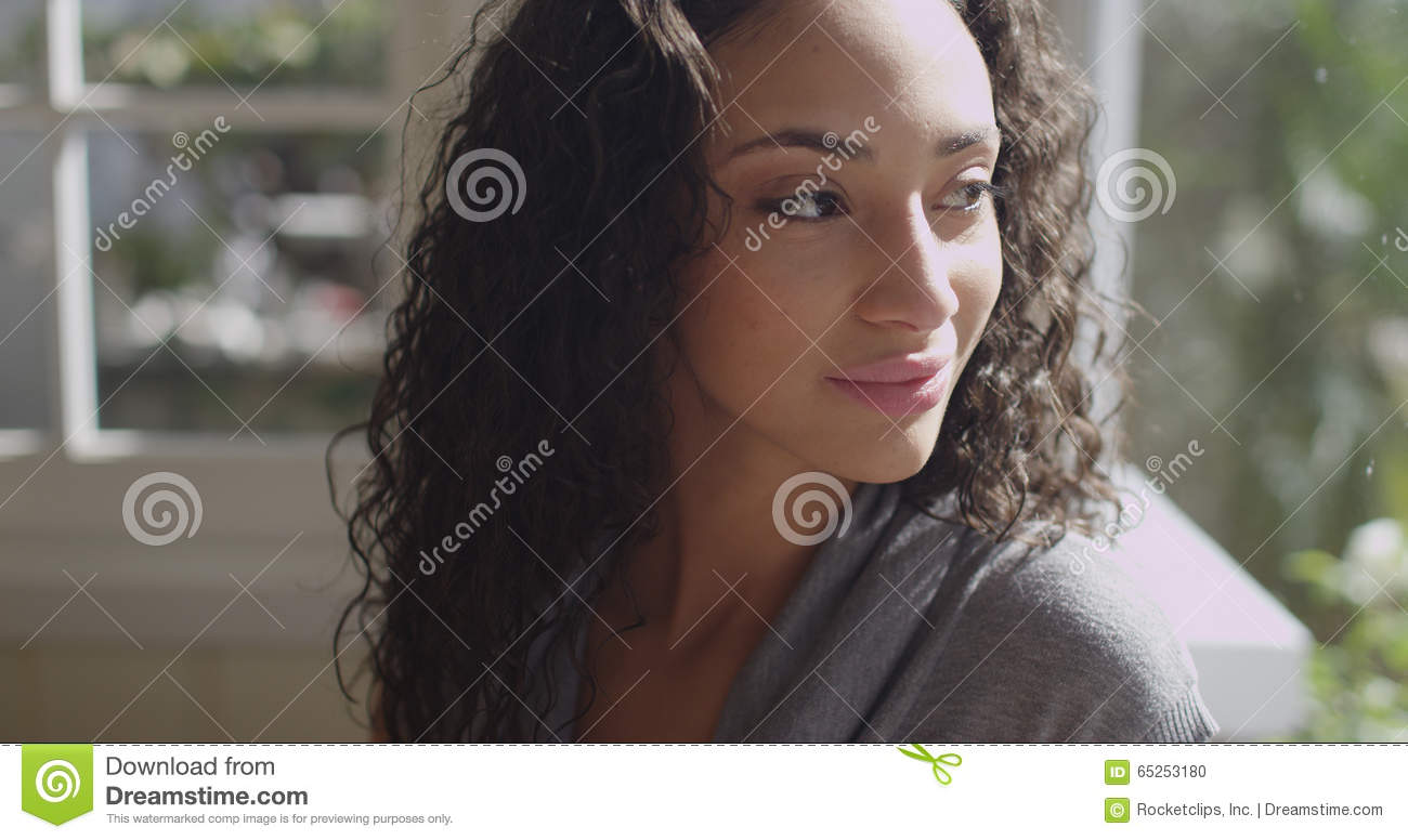 Beautiful young latino woman looking out a window
