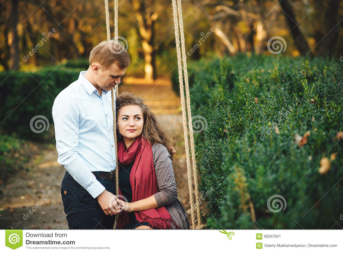 Beautiful young loving couple walking outdoors at the park.