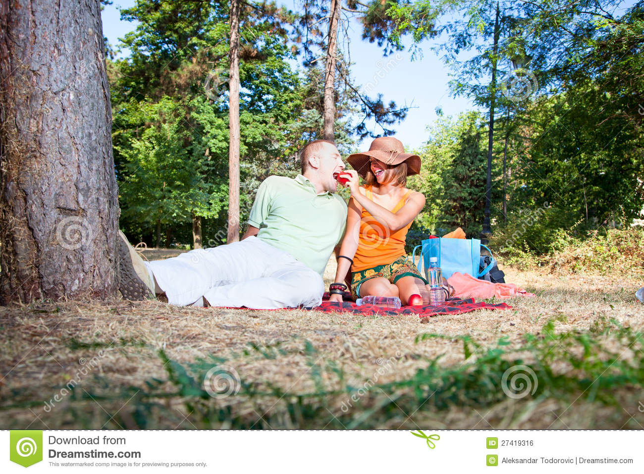 Beautiful young man and woman on picnic in forest