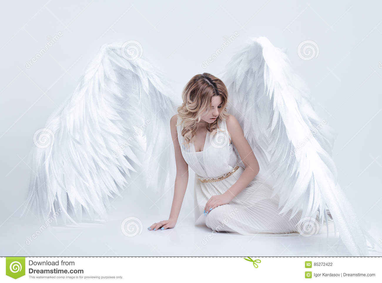 Beautiful young model with big angel wings sitting in the studio