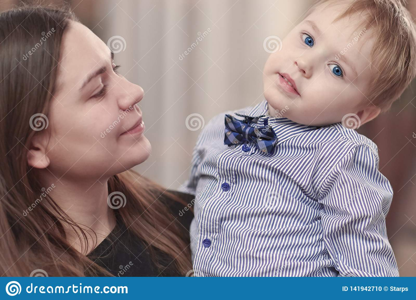 Beautiful young mother with a baby boy in her arms at home. Happy family and motherhood concept.