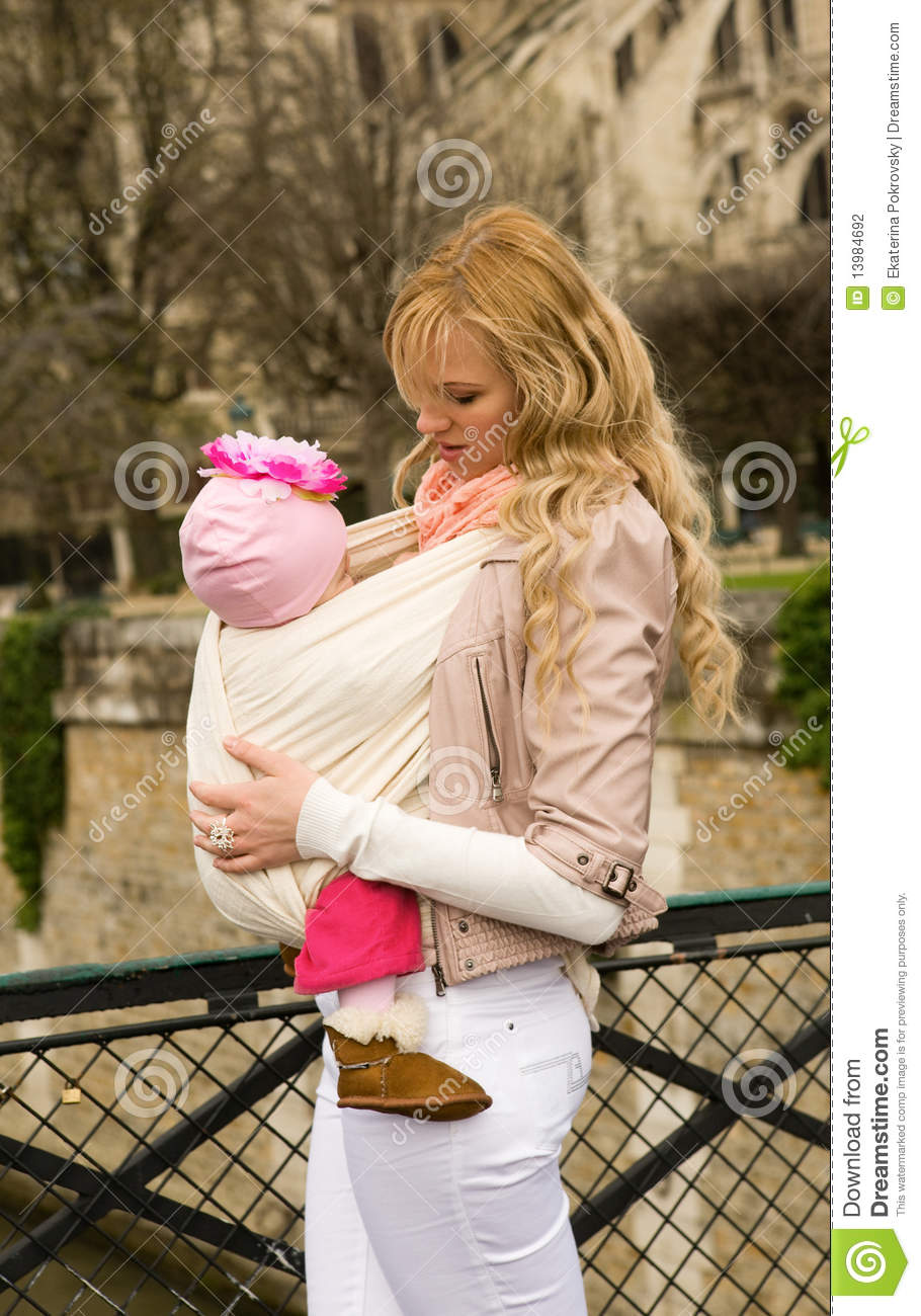 Beautiful young mother with baby daughter in sling