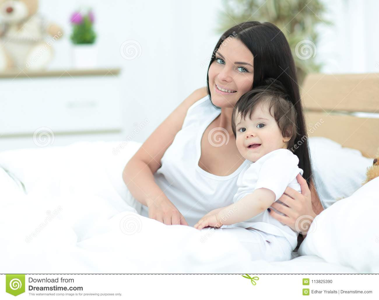 Beautiful young mother with a baby lying in bed and smiling