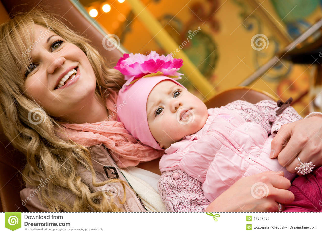 Beautiful young mother with baby on merry-go-round