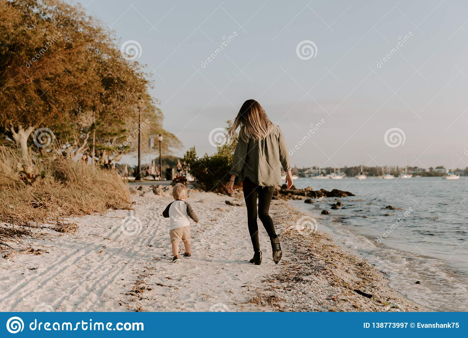 Beautiful Young Mother and Cute Little Boy Son Walking and Enjoying the Nice Outdoor Weather on the Sandy Beach next to the Ocean