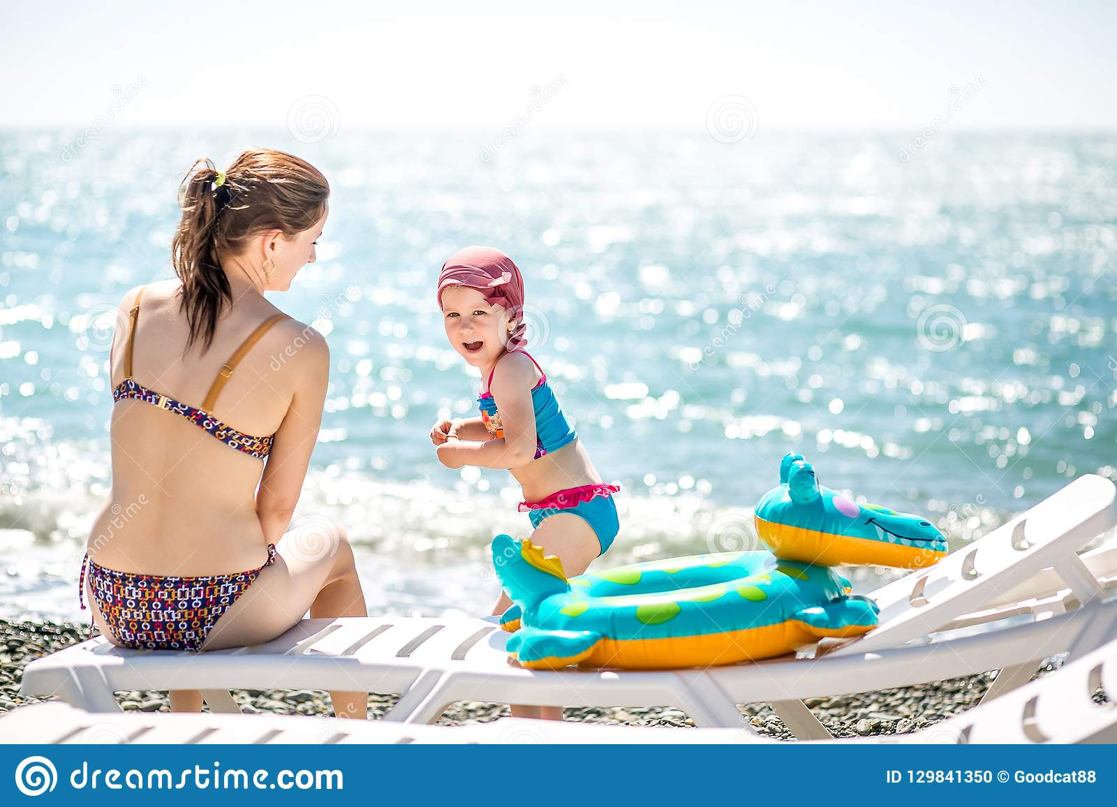 Beautiful young mother and daughter having fun resting on the sea. They sit on the beach with pebbles on a deck chair, little girl