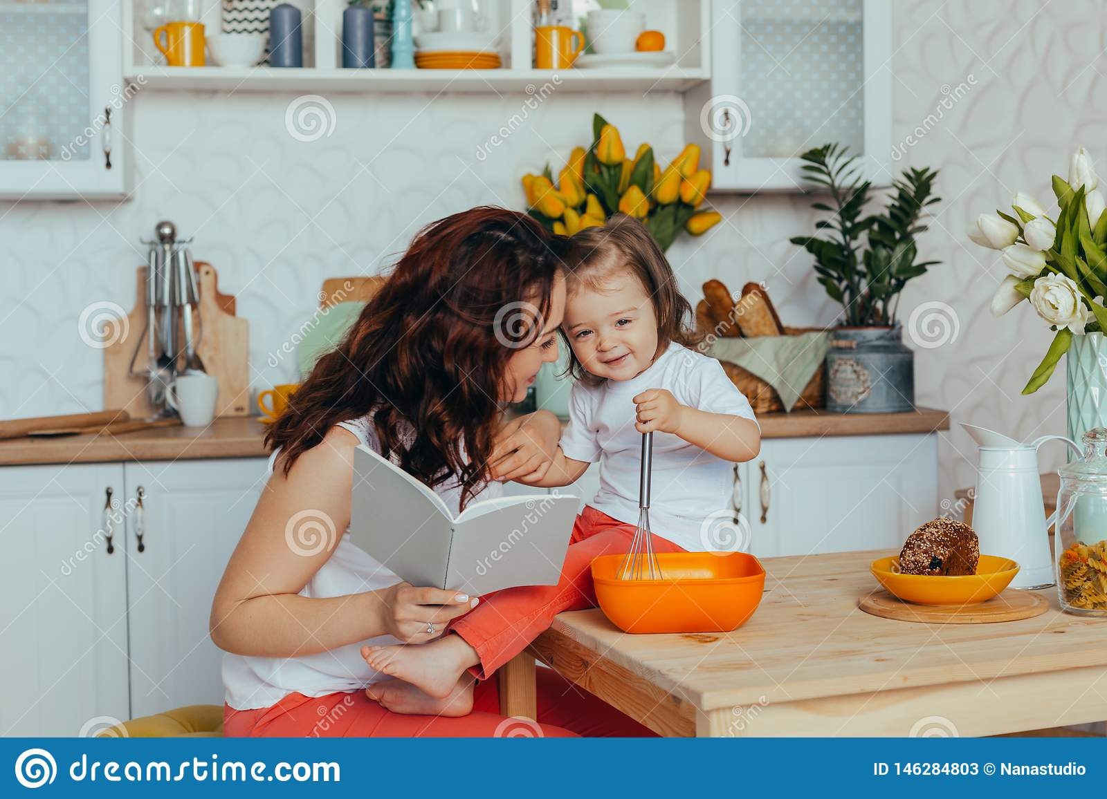 Attractive young woman and her little cute daughter are cooking on kitchen