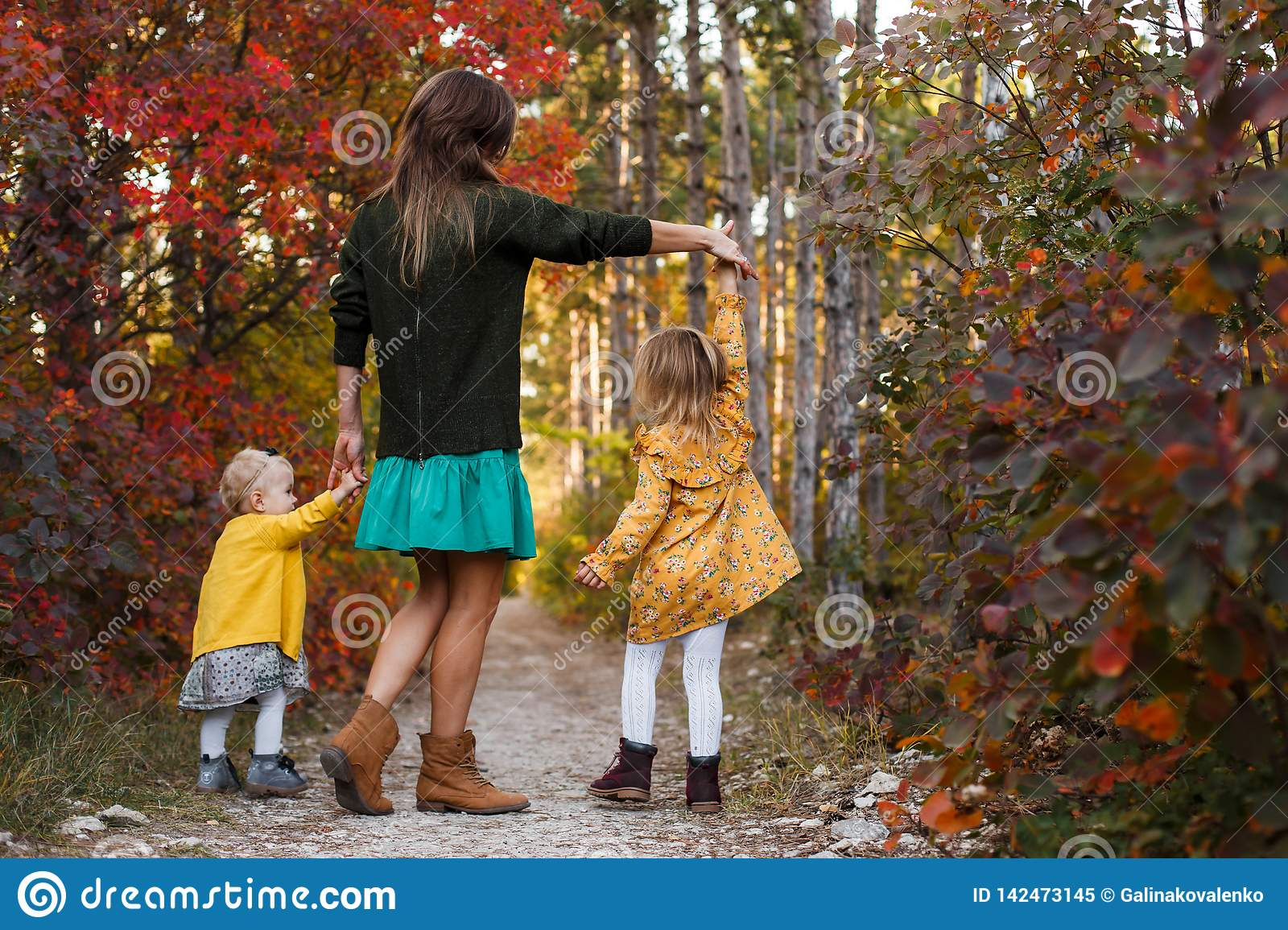Beautiful young mother and her little daughter walking in summer park. Woman and cute kid girl spending time together