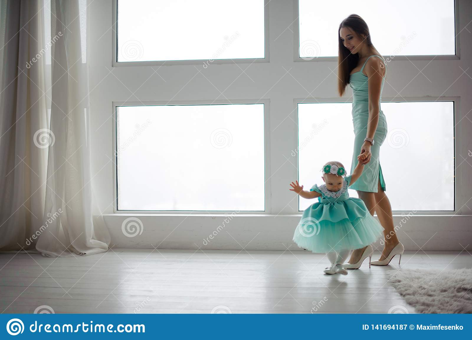 Beautiful young mother hold her daughter hand and walking in the room