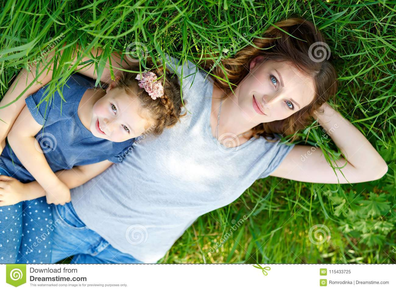 Beautiful young mother and little daughter lying on green grass and resting
