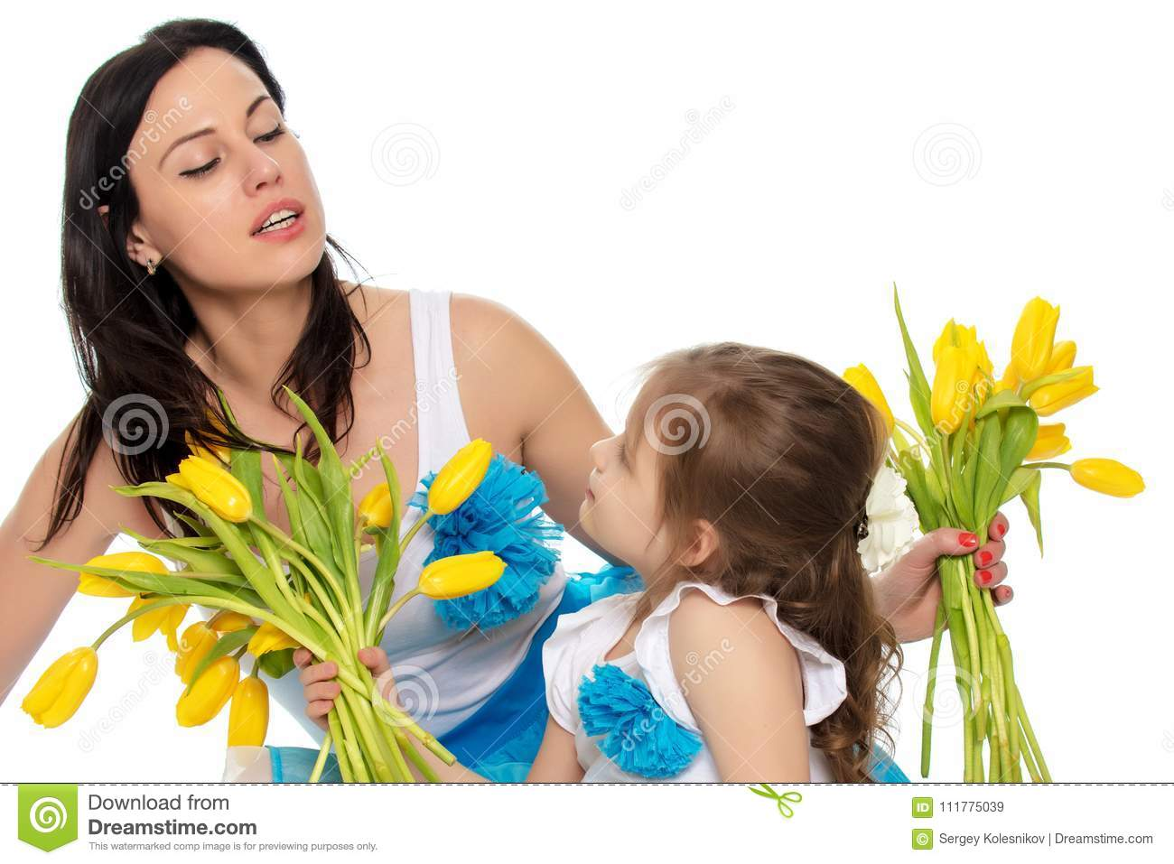 Mother and daughter smelling yellow tulips.