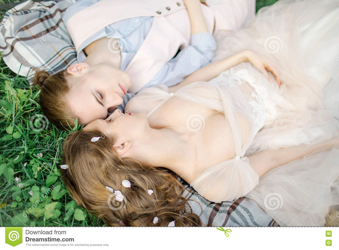 Beautiful young newlyweds couple in love laying on grass