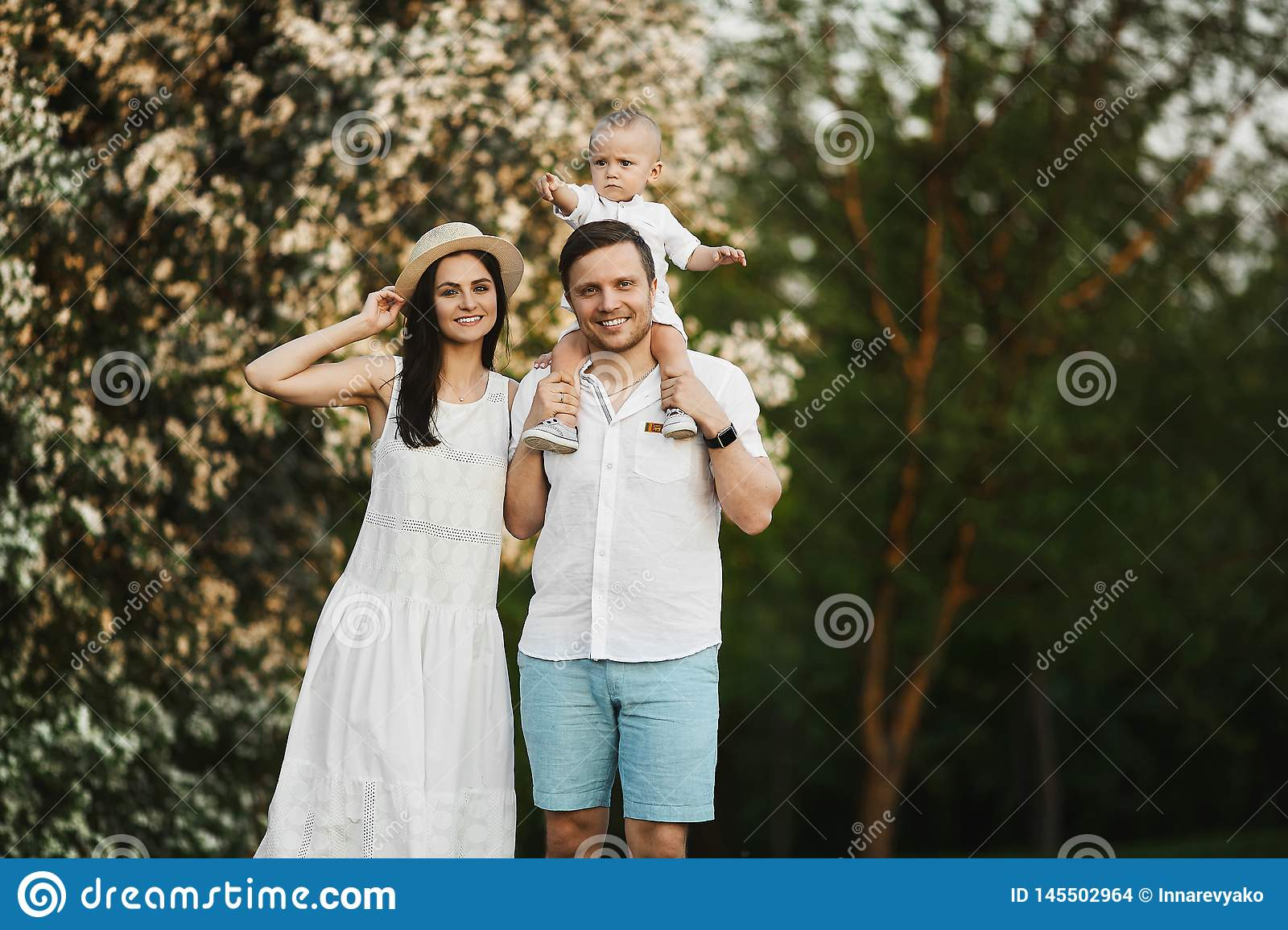 Beautiful young parents and their cute little son have fun near flowering trees, happy family