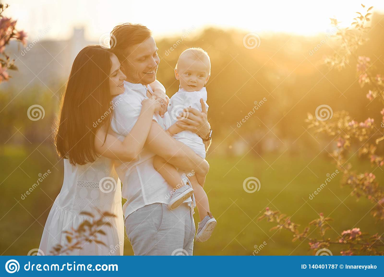 Beautiful young parents and their cute little son hugging and smiling at the sunset