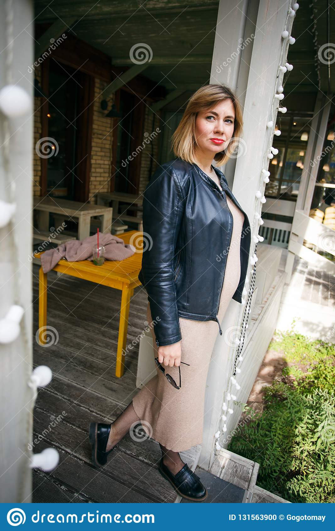 Beautiful young pregnant woman wearing dress and leather shirt resting in city park cafe, stylish pregnancy shot
