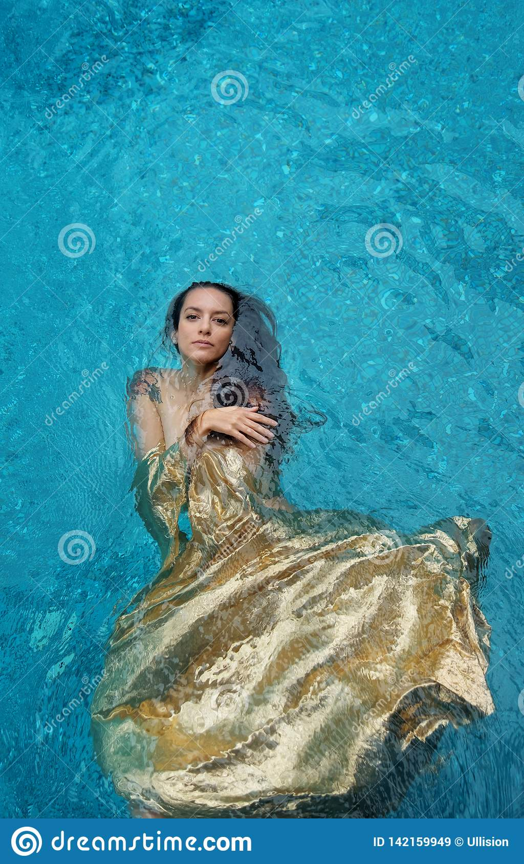 Beautiful young proud woman in golden dress, evening dress floating weightlessly elegant floating in the water in the pool dark