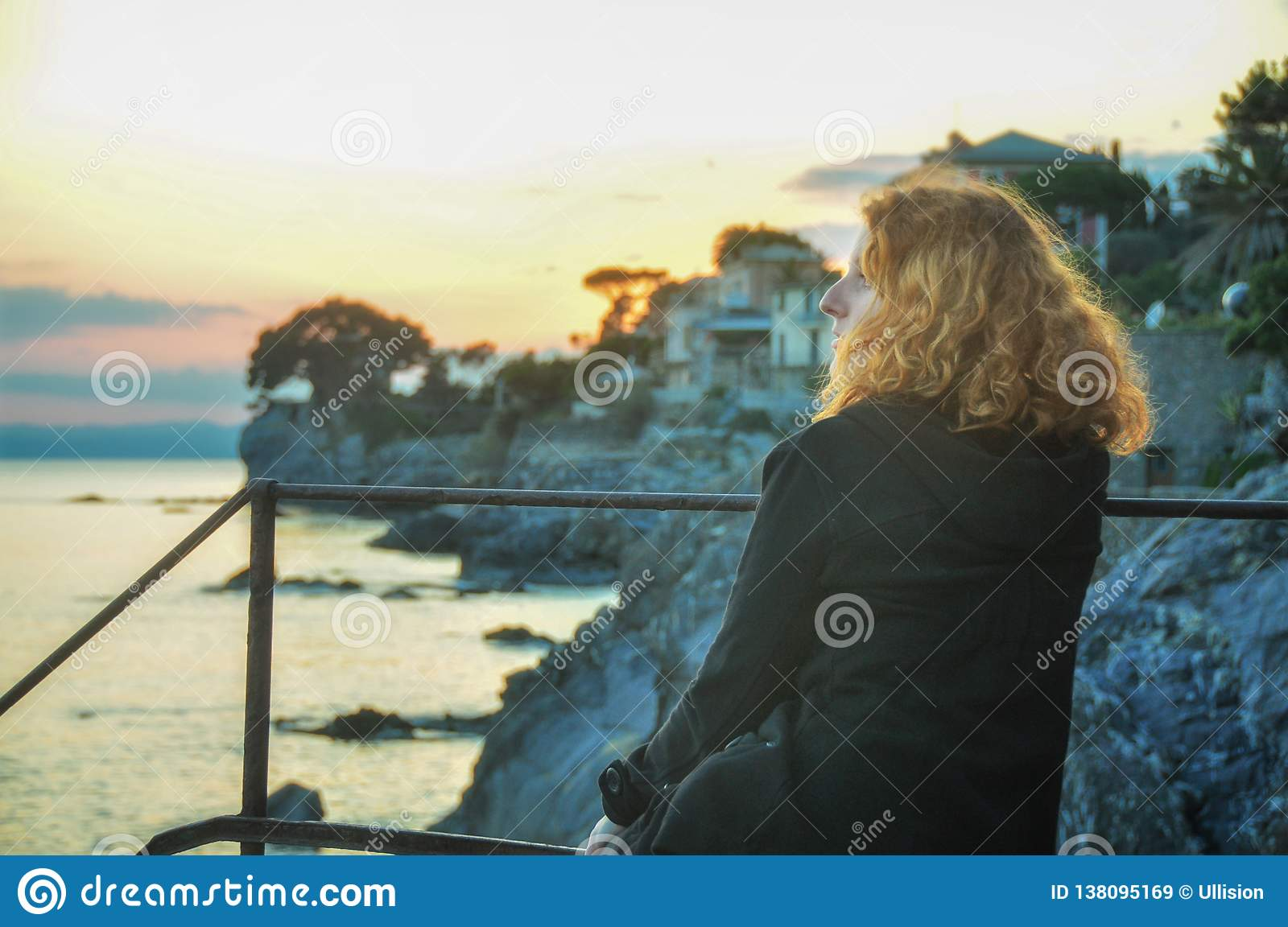 Beautiful young red-haired woman, at the seaside in the fishing village in Liguria, Italy enjoys the sunset