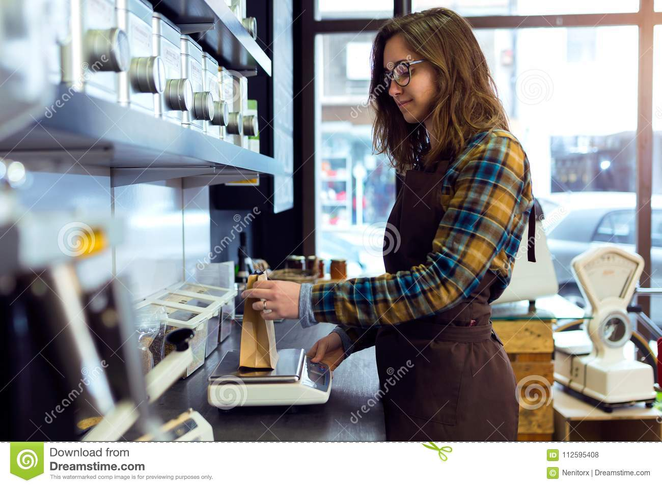 Beautiful young saleswoman weighing coffee beans in a retail store selling coffee.