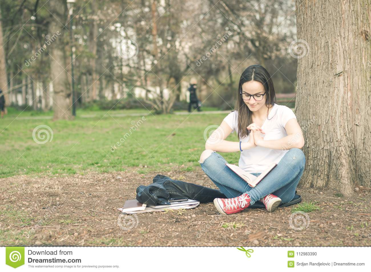 Beautiful young school or college girl with long hair and eye glasses sitting on the ground in the park reading the books and stud