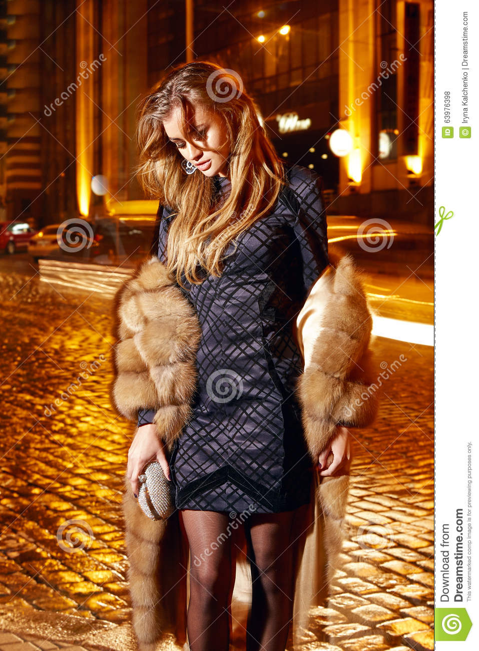 Beautiful young blonde wearing evening makeup in elegant fitting dress fashionable stylish expensive fur coat walk night stre