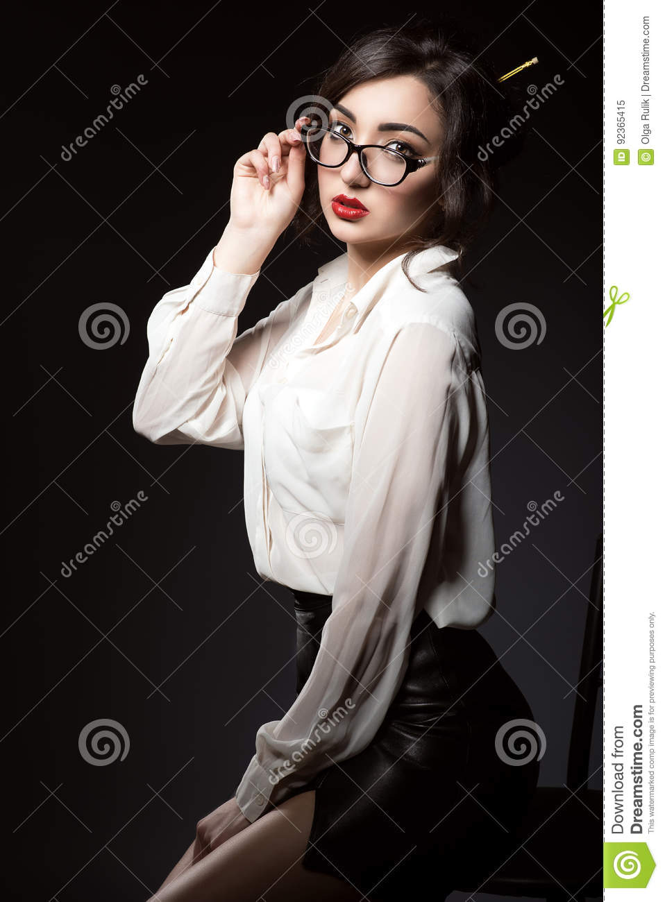 Beautiful young business woman with dark updo hair looking direct over her trendy glasses in modern frame.