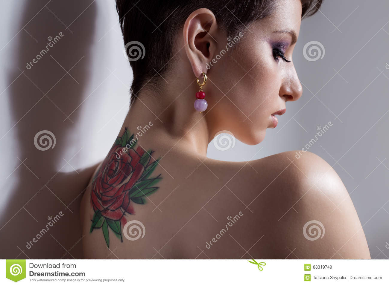 Beautiful young girl with short hair with tattoo on his back is against the wall with bare shoulders sad