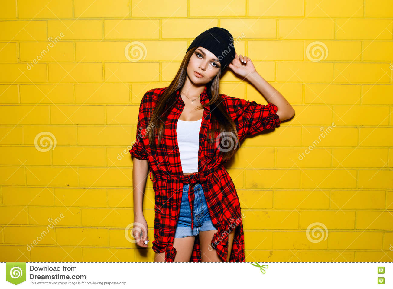 85465d765be Beautiful young hipster girl posing and smiling near urban yellow wall  background in red plaid shirt
