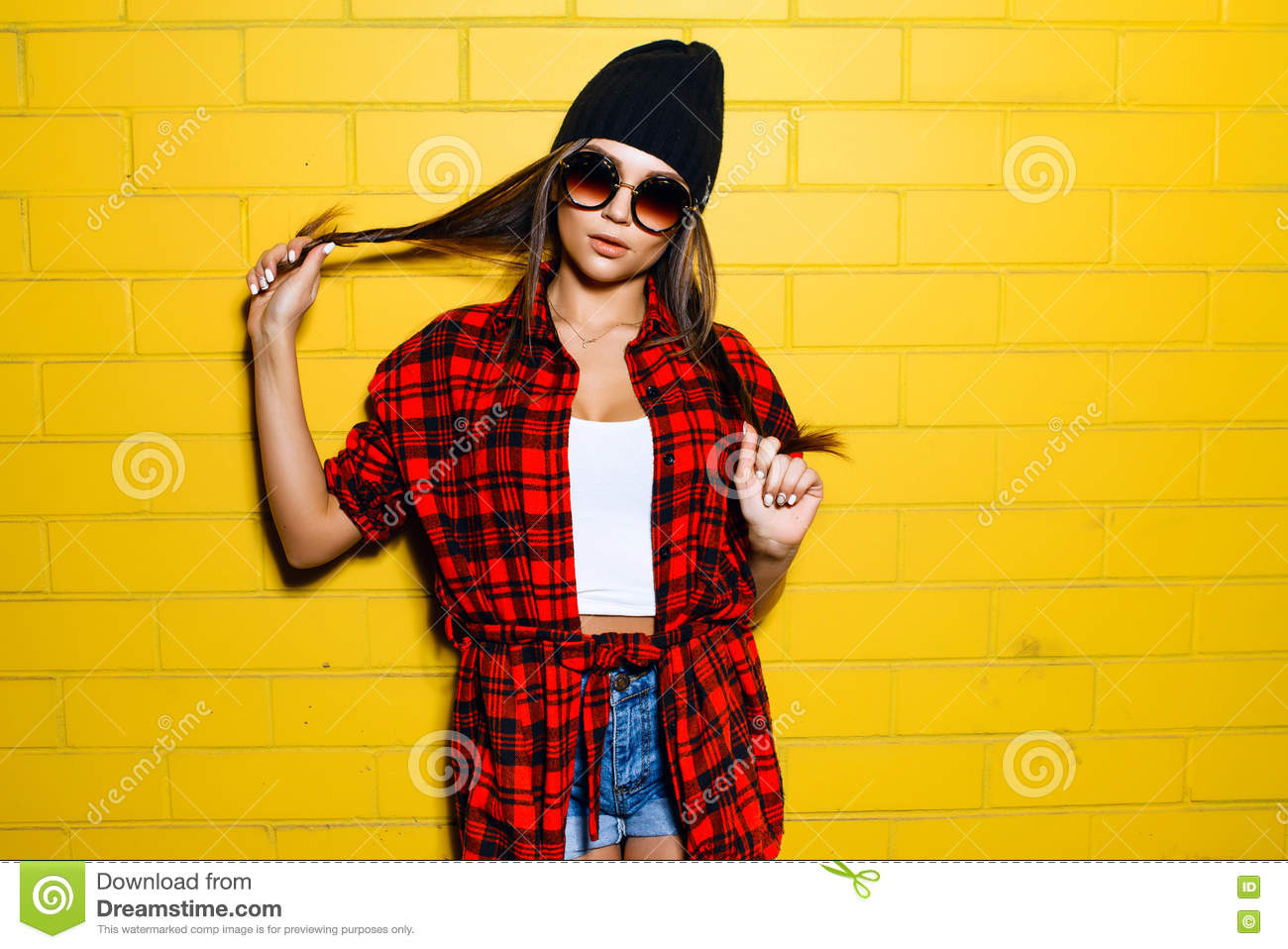 7a96256b5fc Stock Photo  Beautiful Young Hipster Girl Posing And Smiling Near Urban  Yellow Wall Background In Sunglasses