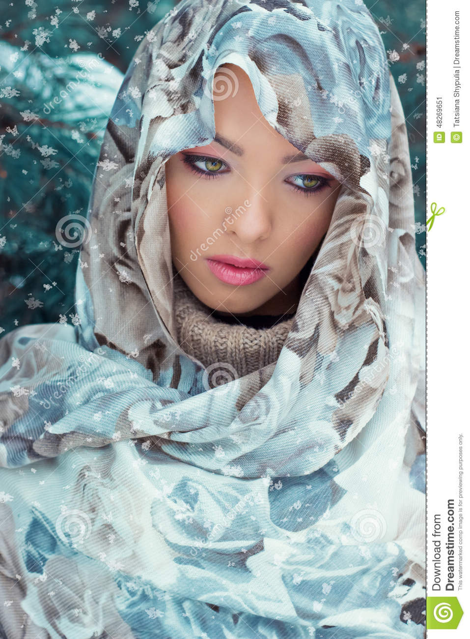 Beautiful young mysterious woman with a scarf on her head standing in the forest near the oil in bright winter day