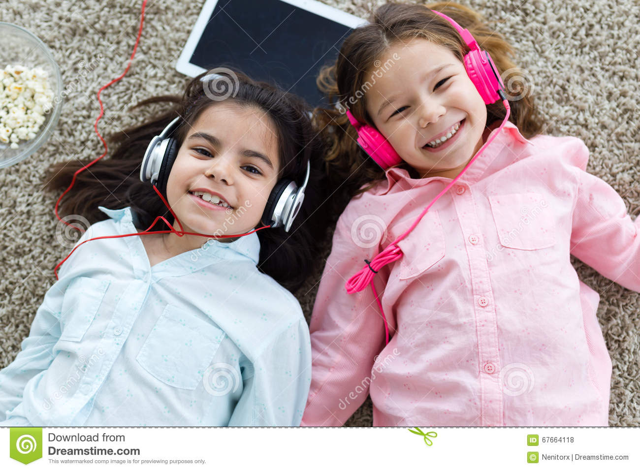 Download Beautiful Young Sisters Listening To Music With Digital Tablet A Stock Photo - Image of people, family: 67664118