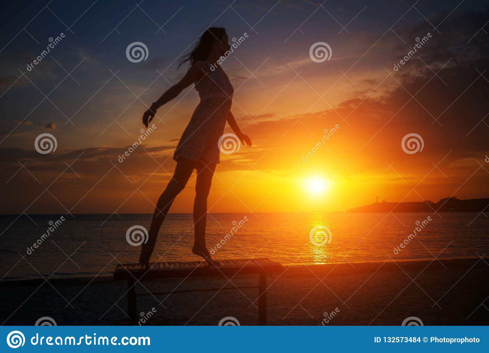 Beautiful young slender woman standing on the beach at sunset, beautiful silhouette against the sky